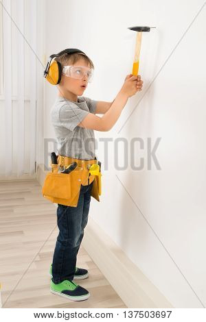 Cute Little Boy Hammering Nail In Wall At Home