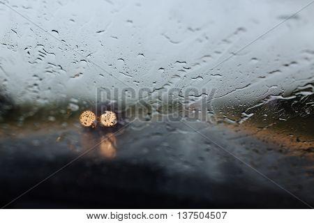 Drive car at heavy rain. Water drops at window