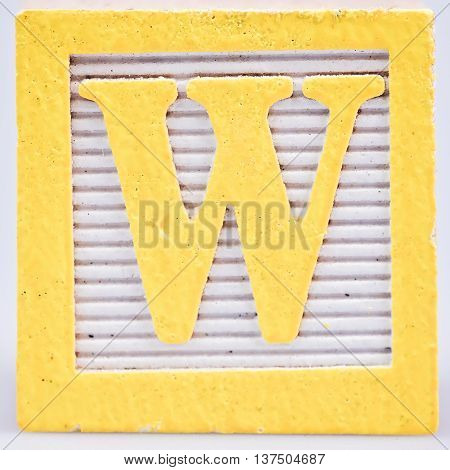 Yellow letter W painted wood block distressed