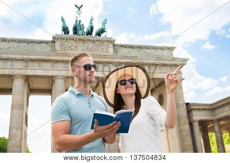Young Couple Reading Tourist Guide In Front Of Brandenburg Gate