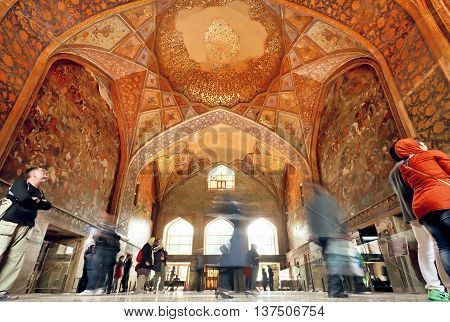 ISFAHAN, IRAN - OCT 17, 2014: Crowd of tourists inside the historical hall with fresco of palace Chehel Sotoun on October 17, 2014. Safavid era Forty Columns palace was built in 1647 in Esfahan.