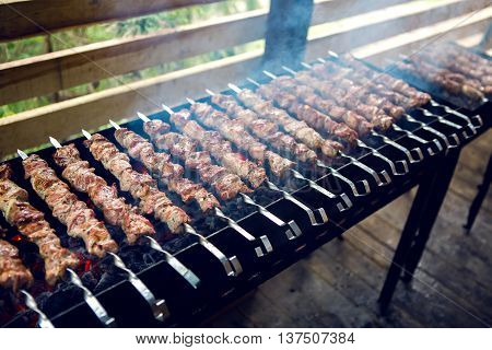 large number of preparing kebabs on the grill with coals and smoke under a canopy