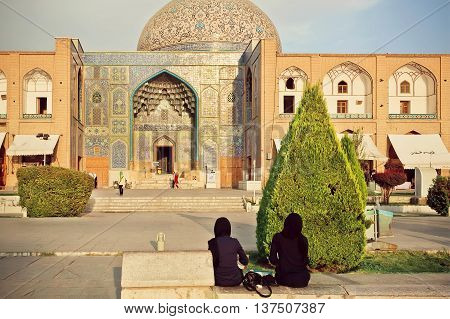 ISFAHAN, IRAN - OCT 14, 2014: Two women in traditional hijab meeting near historical mosque Masjed-e Sheikh Lotfollah on October 14, 2014 in Middle East. Other called Masjed-e Lotfollah built in 1619