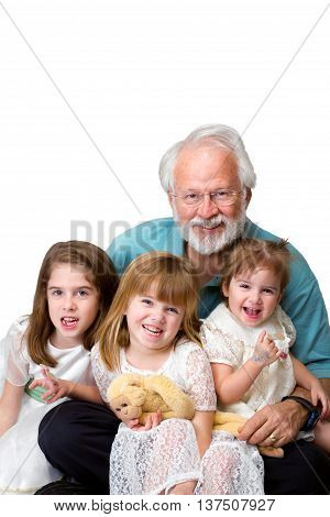 A senior man with his three young granddaughters sitting in his lap. They are in front of a white background and are isolated with a clipping path.