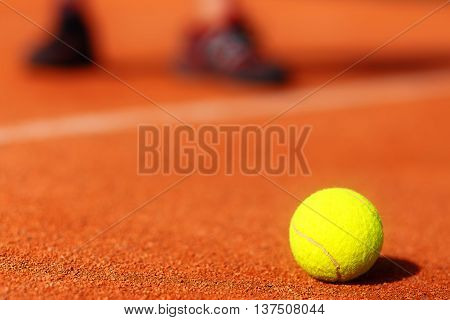 tennis court with tennis ball and man legs on background