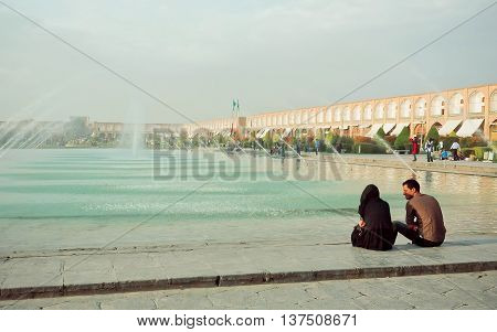 ISFAHAN, IRAN - OCT 16, 2014: Young couple meeting and talking near a fountain of popular Imam Square on October 16, 2014. Naqsh-e Jahan or Imam Square constructed in 1598. UNESCO's World Heritage Sites