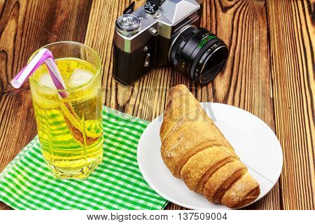 Glassful of lemon soda water with ice and tubule on green napkin. croissant vintage camera wooden table