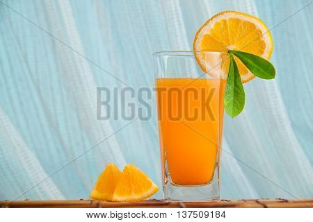 Fresh squeezed orange juice with sliced oranges and green leaf with sea on a background. Healthy drink in the morning.