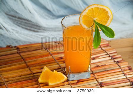 Fresh squeezed orange juice with sliced oranges and green leaf. Healthy drink in the morning.