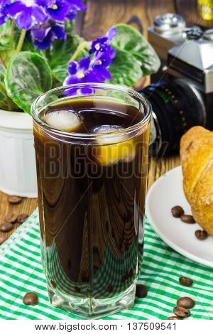 Glassful of black coffee with ice on green napkin. croissant vintage camera flowerpot wooden table selective focus.