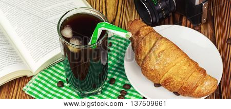 Glassful of black coffee with ice and tubule on green napkin. croissant vintage camera open book flowerpot wooden table travel concept.