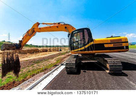 Excavator working on road and highway construction site
