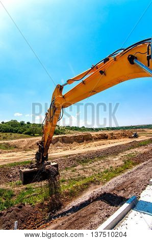 Close-up Of Excavator While Working In Road And Highway Construc