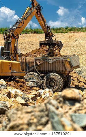 Excavator Loading Heavy Duty Dumper Truck With Rocks On Construc