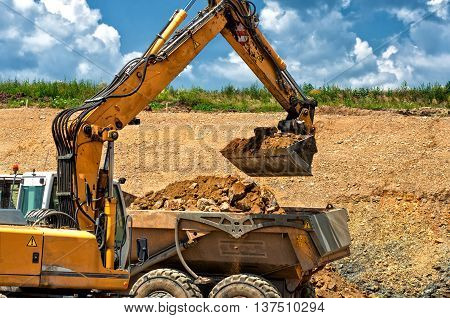 Professional Construction Worker With Excavator Loading Rocks In