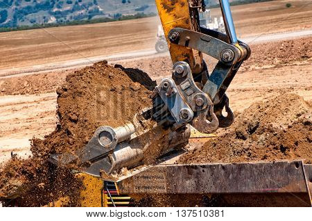 Close-up Of Heavy Duty Excavator Scoop Loading A Dumper Truck Wi