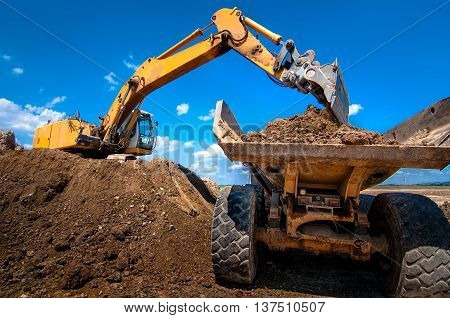 Yellow Excavator Loading Soil  Into A Dumper Truck On Constructi