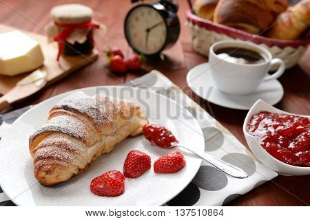 Croissant and a strawberry jam on the wooden background