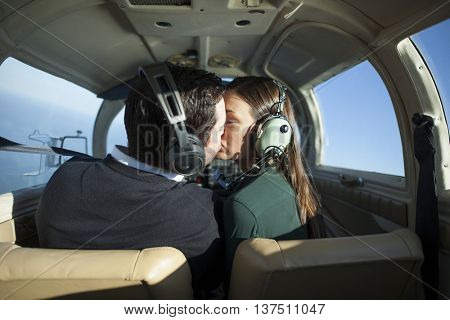 Young jet setting couple kiss in private plane