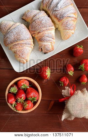 Croissants and a strawberry jam on the wooden background