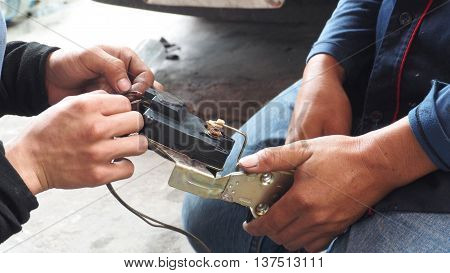 Asian Thai Mechanic check and repair electric current car lock this use at the door.