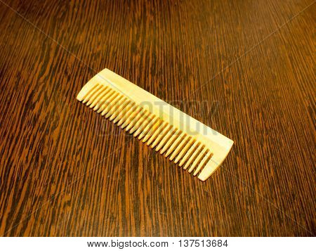 Wooden comb for hair on the table dark wood veneer