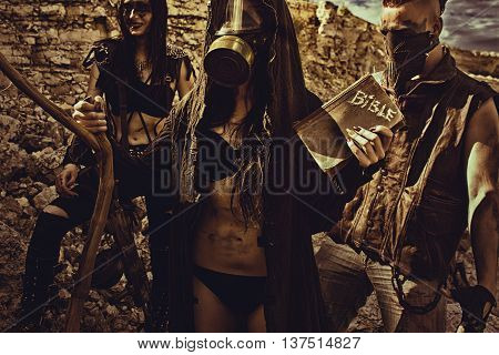 Seductive girl in cloack and two raiders posing on a post-apocalyptic wasteland