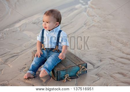 A one year old baby boy sitting on a blue, wooden crate. Shot outdoors on a sandy beach.