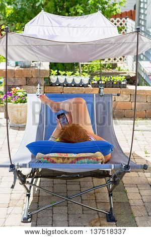 Rear view of person using phone while laying down on cot with shade on outdoor brick patio with plants on wall