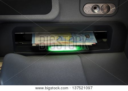 euro bank notes in the slot of a atm ready to take out among them displaying a green lamp