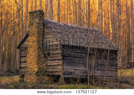Old house in the forest of Smoky mountains at sunset time.