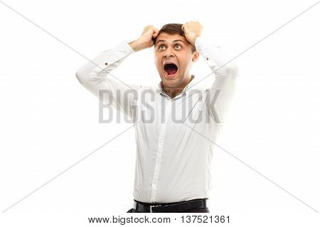 Portrait of handsome screaming businessman holding his head isolated on white