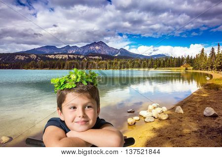 Canadian Rocky Mountains. The picturesque oval lake with clear water. The beautiful boy in carnival wreath on the bank of lake