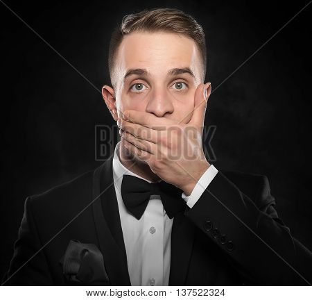 Scared man in suit hand covering mouth over dark background.