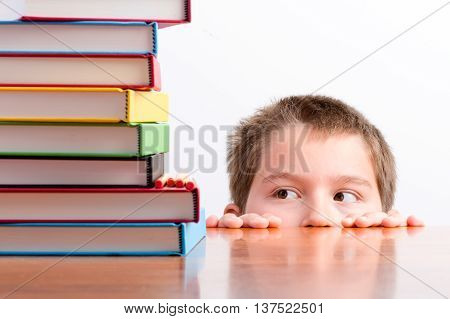 Thoughtful Young Schoolboy Eyeing Up His Books