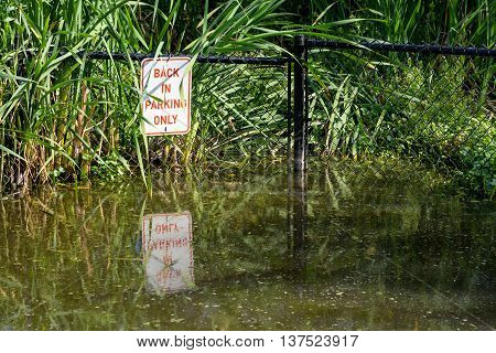 Flooded parking space, with fence and sign
