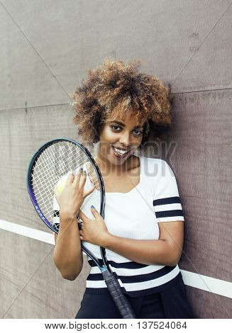 young stylish mulatto afro-american girl playing tennis, sport healthy lifestyle people concept, smiling happy woman