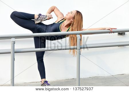 Young fitness woman with a beautiful figure with legs stretched before exercise in the fresh air, the female runner during fitness training