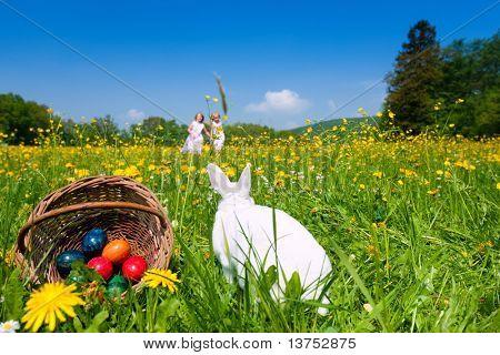 Osterhase mit Eier auf einer Wiese im Frühling, zwei Kinder im Hintergrund