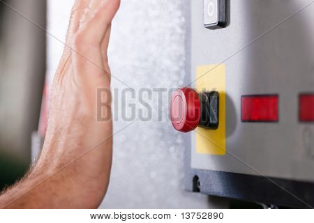 Man is shutting off a machine with the emergency button �¢�?�? probably in a case of danger