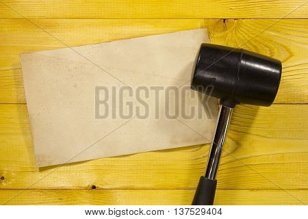 Black rubber hammer on a brown wooden background