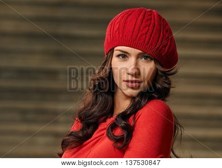 Portrait of a beautiful young woman with background stairs outdoors. beautiful young woman smiling. wearing red dress, beret, black gloves