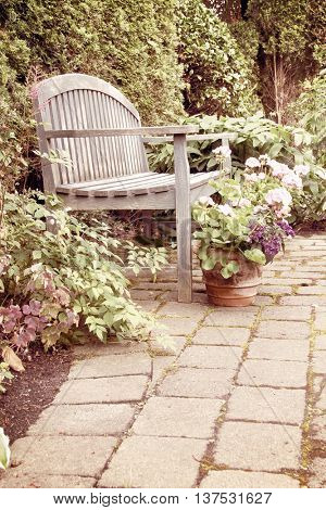Rustic garden bench and pink geraniums in vintage.