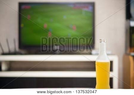 home interior with a bottle of beer in front and a TV broadcasting a soccer match at backgroud
