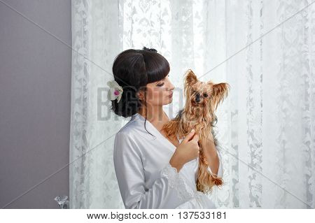 Girl holds a Yorkshire terrier. Home pet. Pedigree dog. Funny animals.