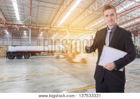 Businessman checking complete product for import and export with forklift loading goods in warehouse background for import export business.