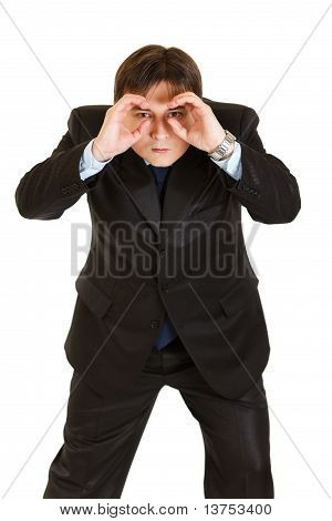Concentrated businessman making binoculars with hands and looking through isolated on white
