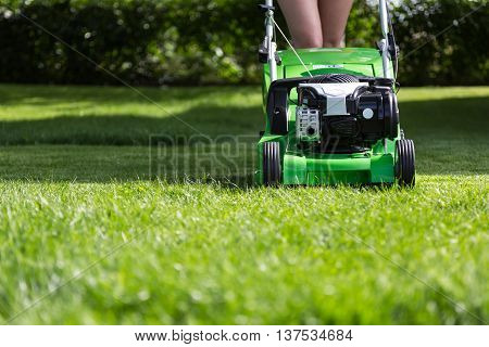 Young woman mowing the lawn.  Lawn mower green