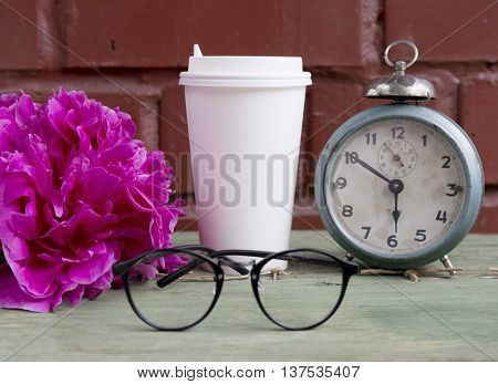 Cardboard cup hot coffee with old alarm clock, peony and black glasses on brick background.