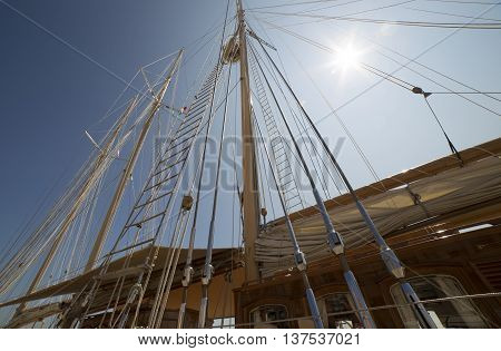 Masts sea yacht on background of the sun